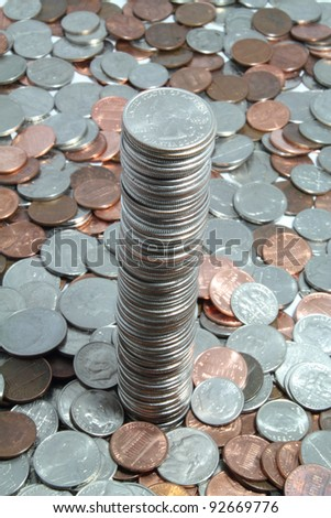 Tall tower of quarters coming out of a pile of coins.