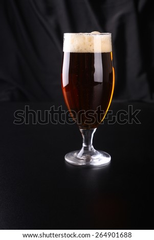 Tall tulip glass of amber ale over a dark background