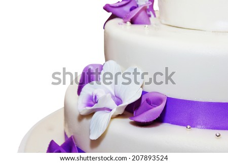 Tall wedding cake with purple ribbon and flower decorations - stock photo