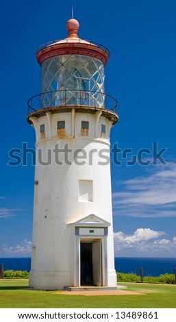 Tall white stucco lighthouse with red roof (Kilauea, Kauai) - stock photo