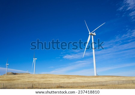 Tall white windmills sit along a ridge line in the American midwest. - stock photo