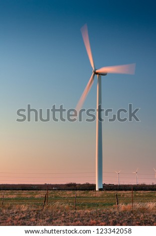 Tall wind turbine in a field in West Texas.  Blades are showing motion blur