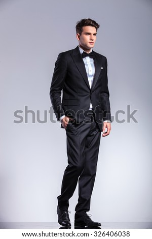Tall young business man holding his hand in pocket while walking on studio background.