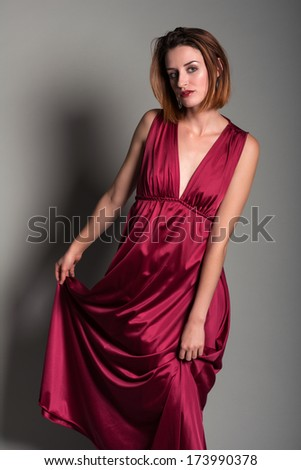 Tall young redhead in a long red dress
