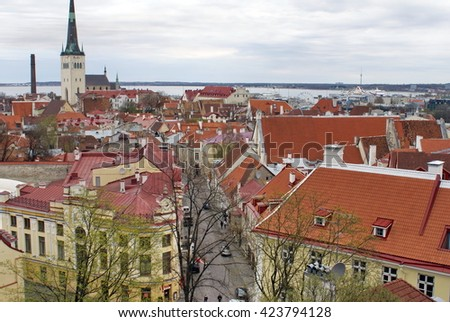 TALLINN, ESTONIA - CIRCA MAY 2012: Red tile roofs of the Old Town with the spire of Saint Olaf's Church, and the port in the distance - stock photo