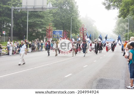 TALLINN, ESTONIA - JULY 05, 2014: Parade of the Estonian XXVI National song and dance festival called Aja Puudutus, Puudutuse Aeg on a foggy day in Tallinn, Estonia on July 05, 2014