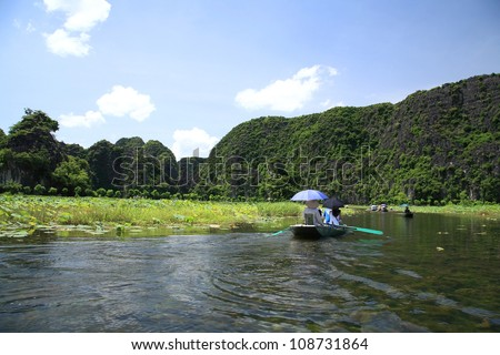 Tam Coc national park: small boats are sailed by sailors' feet to see rice fields , three caves, and limestone mountains along the Ngo Dong river in Ninh Binh, the northern of Vietnam - stock photo