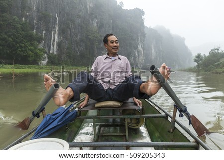 Tam Coc, Vietnam - March 19, 2016. Unidentified man rowing on a wood boat for carrying tourists in Ngo Dong river. Tam Coc is a popular tourist destination near Ninh Binh, in northern Vietnam.