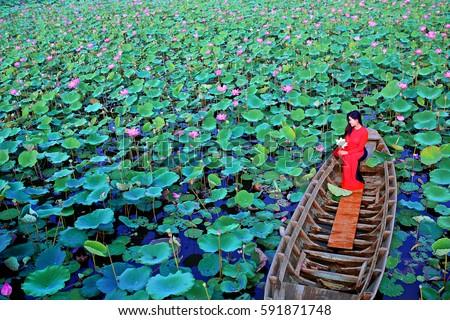 Tam Da lotus lake, Ho Chi Minh city, Vietnam - February27, 2017: Vietnamese woman wearing red traditional clothing (Ao dai) sitting on sampan in lotus lake