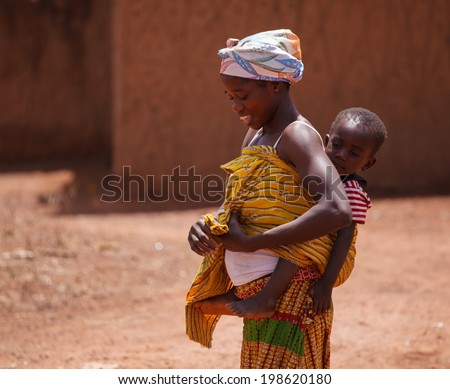 TAMALE, GHANA - MARCH 24: Unidentified African woman carrying her son on back on March 24, 2014 in Tamale, Ghana. Ghana is one of the most popular tourists destination in Africa.
