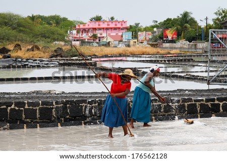 TAMARIN, MAURITIUS - OCTOBER 30: Two unidentified women desalinating water, October 30, 2013 in Tamarin, Mauritius. - stock photo