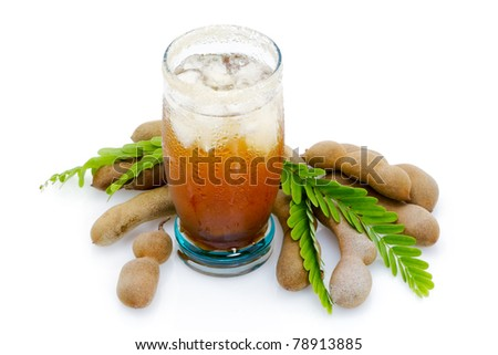 Tamarind juice in a glass surrounded by fresh ripe tamarinds and tamarinds leaves