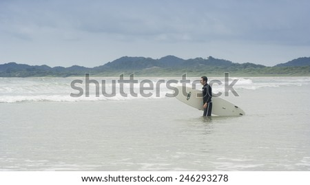 TAMARINDO, COSTA RICA - SEPTEMBER 13, 2008: Young man going to surf in Tamarindo, Costa Rica. Tamarindo is located on the Northern Pacific Coast and a leading surfer hotspot. - stock photo
