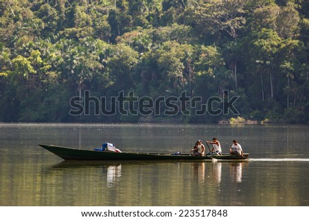 TAMBOPATA, MADRE DE DIOS, PERU - CIRCA 2013: A boat with people navigate the Sandoval lake circa 2013 in Tambopata, Peru. - stock photo