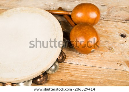 Tambourine and maracas on a wooden table - stock photo