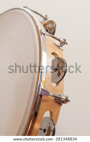 Tambourine in vertical position with nobody holding on  a beige background - stock photo
