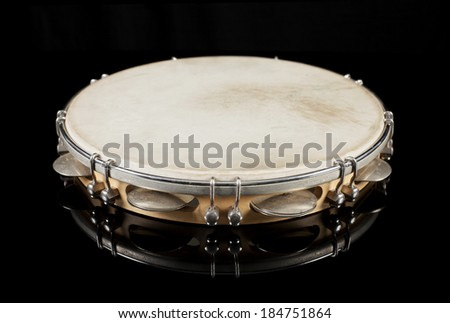 Tambourine on black reflective background
