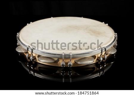 Tambourine on black reflective background - stock photo