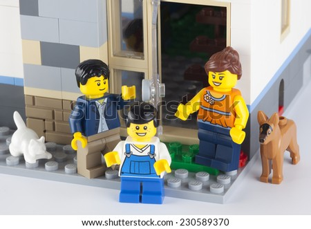 Tambov, Russian Federation - January 08, 2014 Happy LEGO family standing near his home with pets. There are minifigures of mom, dad, son, cat and dog.  - stock photo