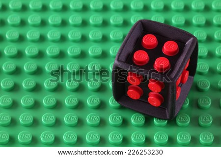 Tambov, Russian Federation - May 08, 2013:  LEGO Cube on a green baseplate. Studio shot. LEGO is a popular line of construction toys manufactured by the Lego Group (Billund, Denmark).