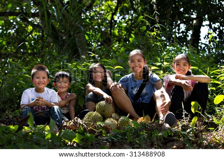 Tambunan, Sabah August 30, 2015 : A group of happy Dusun children resting after picking up fallen durians at the orchard. Durian is a local fruit with strong sweet smell and thorny skin.