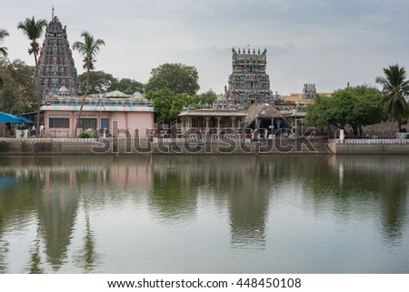 Tamil Nadu, India - October 18, 2013: Pillayarpatti Karpaga Vinayagar temple seen from the other side of the temple pond. Gray-blue sky, green trees envelope the Gopurams and entrance buildings. - stock photo