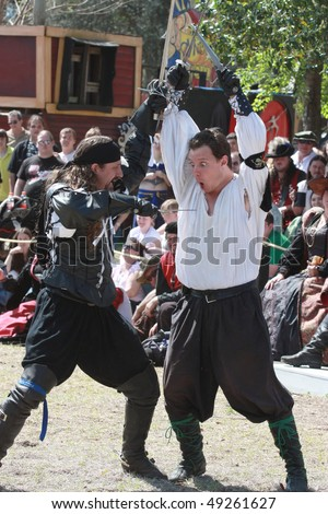 TAMPA FLORIDA- MARCH 13: Gentlemen dress up in Renaissance clothing sword fight during a show for the audience on March 13, 2010 in Tampa, Florida. - stock photo