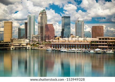 Tampa Florida skyline with sun,  clouds and reflections - stock photo