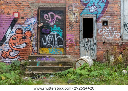 Tampere, Finland - September 26, 2014: Closed doors of a partly abandoned industrial building with graffiti on the wall.