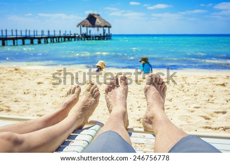 Tan Feet of a couple on lounge chairs enjoying a beach vacation while watching their kids play in the sand - stock photo