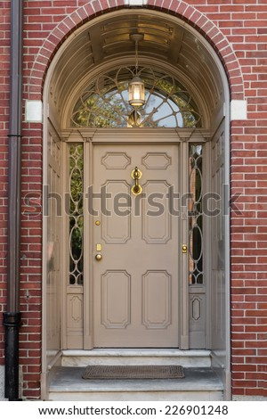 Tan Front Door with Lunette Window and Arch in Brick Building - stock photo