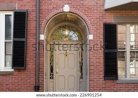 Tan Front Door with Lunette Window and Arch in Brick Building with Black Shutters and Windows in Frame - stock photo