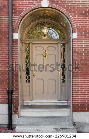Tan Front Door with Lunette Window and Arch in Brick Building with Pipe - stock photo