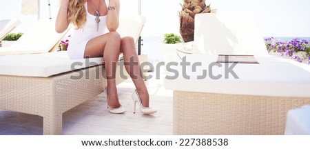 Tan sexy woman legs in white fashion shoes on a on a sun lounger on the beach. - stock photo