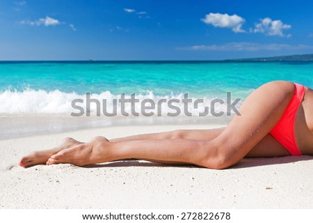 Tan slim legs lying on white sandy beach near sea, no face. Free copyspace background - stock photo