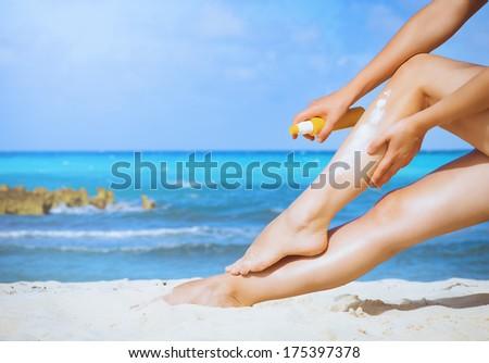Tan Woman Applying Sunscreen on Legs  - stock photo