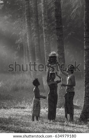 Tanah Embet village, West Lombok, Indonesia - April 23, 2017 : Young man giving a helping hand to a girl carrying a hindu offering on her head