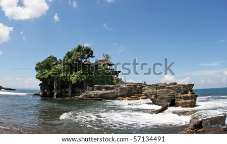 """Tanah Lot means """"Land Sea"""" in Balinese language Located in Tabanan, about 20 km from Denpasar, the temple is on offshore rock which has been shaped continuously over the years by the ocean tide. - stock photo"""