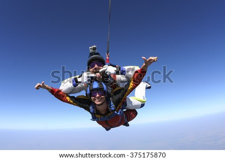Tandem jump. The girl with the instructor in freefall. - stock photo