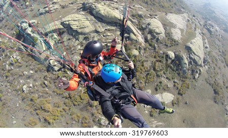 Tandem paragliding over rocky mountains