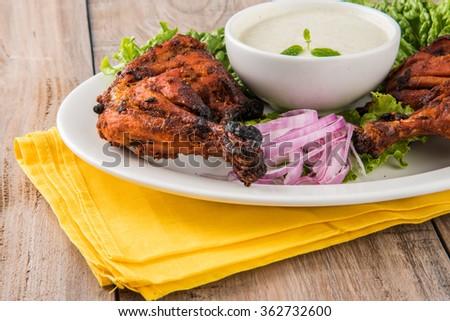tandoori chicken legs, Tandoori Chicken , Indian spicy food, Delicious Tandoori chicken leg pieces with Salad, India - stock photo