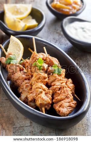 Tandoori chicken skewers, served with yogurt, lemon wedges and mango chutney. - stock photo