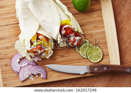 tandoori masala spiced tortilla wraps with lettuce, peppers, lime and onion  - stock photo
