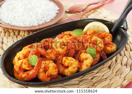 Tandoori prawns on a cast iron sizzle platter, served with basmati rice. - stock photo
