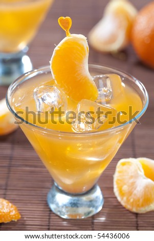Tangerine cocktail on dark wooden table top - stock photo