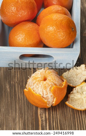 Tangerine fruits in a timber box on a wooden table - stock photo