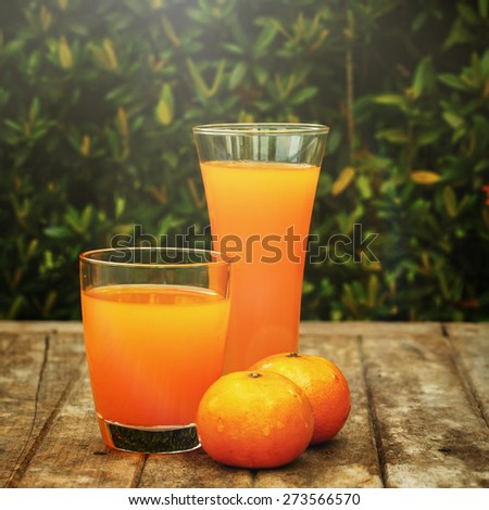 Tangerine juice on a wooden board - stock photo