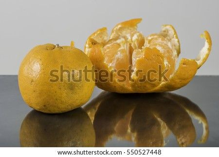 Tangerine on table with reflection
