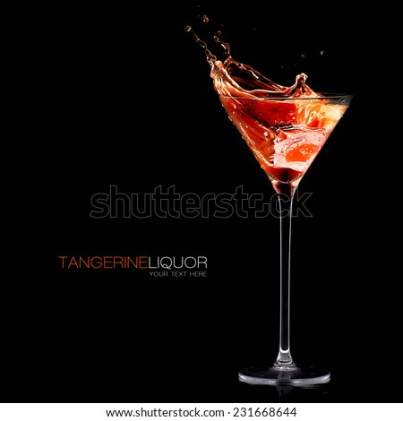 Tangerine Schnapps. Cocktail glass with high stem filled with orange liqueur splashing out on a black background, close-up, template design with sample text - stock photo