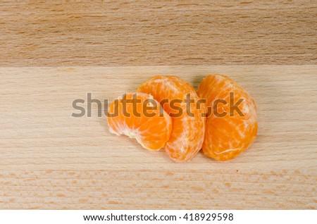 tangerine segments on a wooden table - stock photo